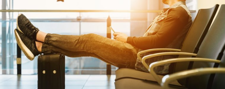 Man sitting in airport chair with feet on suitcase looking at a plane taking off